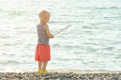 Little boy in a striped T-shirt is standing on the seashore with a wand in his hands. View from the back Stock Images