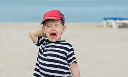 Little boy in a striped T-shirt whimsical cries against the sea. Royalty Free Stock Photography
