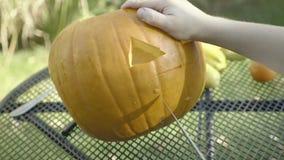 Little boy strokes spoonful Halloween creepy head. Child hands carve halloween pumpkin scarecrow. stock video
