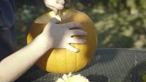 Little boy strokes spoonful Halloween creepy head. Child hands carve halloween pumpkin scarecrow. stock footage