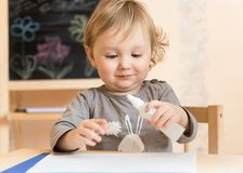 Little boy studies glue Royalty Free Stock Image