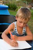 The little boy studies to write. The fair-haired boy writes on a sheet of paper a pencil Stock Image