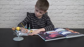 Little boy studying astronomy. Little boy doing homework, studying astronomy using the model of solar system stock footage
