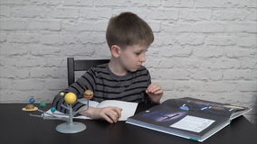 Little boy studying astronomy. Little boy doing homework, studying astronomy using the planetary system stock video footage