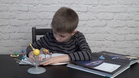 Little boy studying astronomy. Pupil doing homework, writing in the notebook, the book about astronomy and the model of solar system on the table stock video