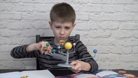 Little boy studying astronomy. Turning the models of planets around the Sun stock video footage