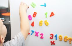 A little boy is studying the magnetic numbers on the fridge. Preschooler training royalty free stock photo
