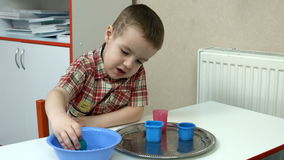 Little boy studying properties of water stock video