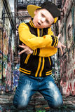 The little boy in the style of Hip-Hop . Children`s fashion.Cap and jacket. The Young Rapper.Graffiti on the walls.Cool rap dj. Stock Photos