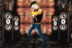 The little boy in the style of Hip-Hop . Children`s fashion.Cap and jacket. The Young Rapper.Graffiti on the walls.Cool rap dj. Royalty Free Stock Photo