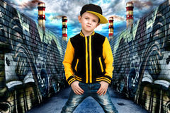The little boy in the style of Hip-Hop . Children`s fashion.Cap and jacket. The Young Rapper.Graffiti on the walls.Cool rap dj. Trendy boy style hip- hop on the royalty free stock photos