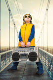 The little boy in the style of Hip-Hop holds a vintage tape recorder. The Young Rapper.Cool rap dj.Vintage Silver Radio boom box. The Young Rapper.Graffiti on stock images