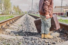 Little boy with suit case on railway Stock Image
