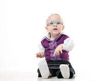 A little boy in a suit and glasses. Dreamily looking up while lying on the floor and playing tablet Royalty Free Stock Images
