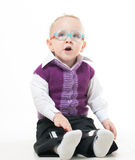 A little boy in a suit and glasses. Dreamily looking up while lying on the floor and playing tablet Stock Images