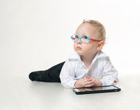 A little boy in a suit and glasses dreamily. Looking up while lying on the floor and playing tablet Stock Images