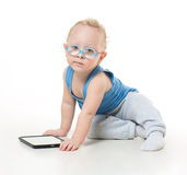 A little boy in a suit and glasses dreamily. Looking up while lying on the floor and playing tablet Royalty Free Stock Photos