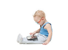 A little boy in a suit and glasses dreamily. Looking up while lying on the floor and playing tablet Stock Photography
