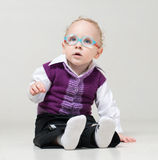 A little boy in a suit and glasses dreamily. Looking up while lying on the floor and playing tablet Stock Image