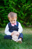 Little boy in a suit playing in the park with a rabbit Stock Photos