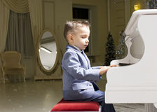 Little boy in a suit playing the piano Stock Photos