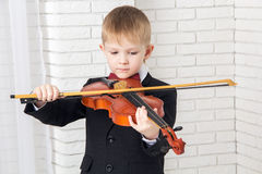 Little boy in a suit playing the violin Stock Photo