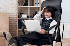 A little boy in a suit presents himself as a businessman. The dark-haired boy plays a rich man. royalty free stock image