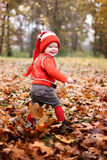 Little boy in a suit with a pumpkin gnome in autumn park Stock Image