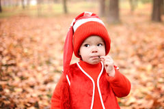 Little boy in a suit with a pumpkin gnome in autumn park Stock Photo