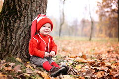 Little boy in a suit with a pumpkin gnome in autumn park Stock Photos