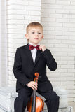 Little boy in a suit sitting with violin Royalty Free Stock Photo