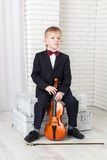 Little boy in a suit sitting with violin Royalty Free Stock Photography
