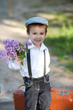 Little boy with suitcase and lilac Stock Images
