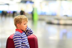 Little boy with suitcase waiting in the airport Royalty Free Stock Photos