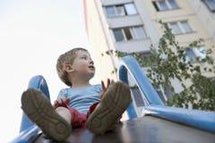 Little Boy sullo scorrevole del campo da giuoco Fotografia Stock Libera da Diritti