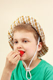 Little boy in the summer hat eating fresh ripe strawberry Royalty Free Stock Photo
