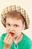 Little boy in the summer hat eating fresh sweet strawberry Royalty Free Stock Photos
