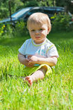 Little boy in the summer park sitting on the grass Royalty Free Stock Image
