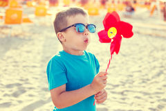 Little boy in sunglasses blowing pinwheel Stock Image