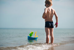 Little boy in sunglasses playing with toy boat Stock Images