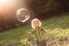 Little boy in the sunset catches soap bubbles stock images