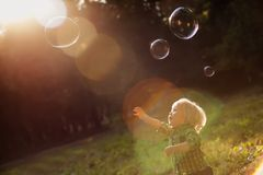 Little boy in the sunset catches soap bubbles Royalty Free Stock Photos