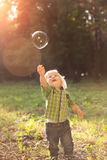 Little boy in the sunset catches soap bubbles stock image