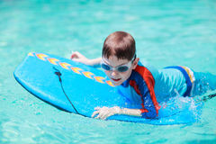 Little boy with surf board. Learning surfing Stock Image