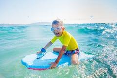 Little boy surfboarding Stock Images