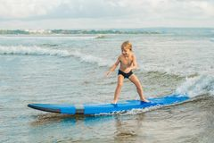 Little boy surfing on tropical beach. Child on surf board on ocean wave. Active water sports for kids. Kid swimming with stock photography