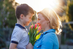 Little boy surprising mom with tulips Stock Photo
