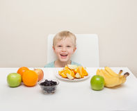 A little boy surround by fruit.  The child is photographed again Stock Photo