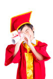 Little Boy sveglio che indossa graduazione rossa del bambino dell'abito con il tocco Immagini Stock