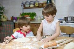 Little Boy sveglio che mostra suo fratello gemello How per appiattire pasta al tavolo da cucina Fotografia Stock Libera da Diritti